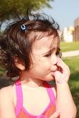 Lilla flicka, suger hennes tumme promenader i parken — Stockfoto