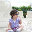 Adorable young baby girl wearing sunglasses in flirting position — Stock Photo #6646060