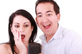 Young pair was surprised, having read on mobile phone sms. — Stock Photo