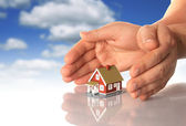Hands and little house. — Stock Photo