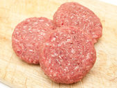 Raw beef burgers close up on a board — Stock Photo