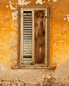Grunge window with blinds and shutter over old orange wall — Stock Photo
