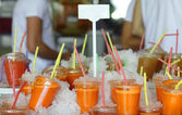 Plastic glasses with cold freshly squeezed carrot juice at Tel-Aviv market — Stock Photo
