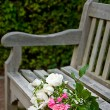 A bunch of roses lying on a park bench — Stok fotoğraf