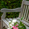 A bunch of roses lying on a park bench - Stock Photo
