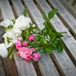 um buquê de rosas, deitado sobre um banco do parque — Foto Stock
