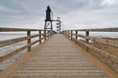 Old lighthouse at the end of a bridge — Stock Photo