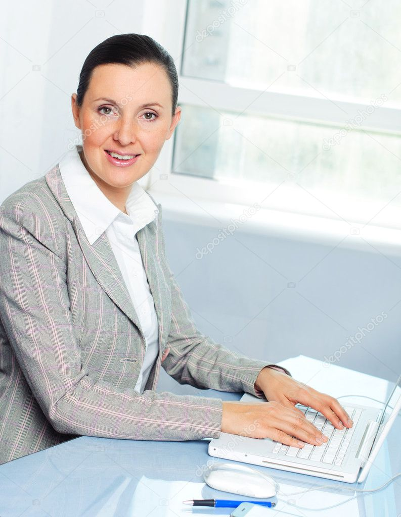 Attractive smiling young business woman using laptop at work desk — Stock Photo #5442585