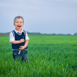 A beautiful little boy staing in the grass — Stock Photo #5528160