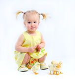 Cute little girl in a yellow dress with really live chickens. — Stock Photo