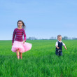 Sister runing with her brather on the grass — Stock Photo