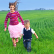 Sister runing with her brather on the grass — Stock Photo #5602659