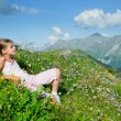 Royalty-Free Stock Photo: Girl lying in a meadow backround Alps