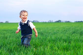 A beautiful little boy runing in the grass — Stock Photo