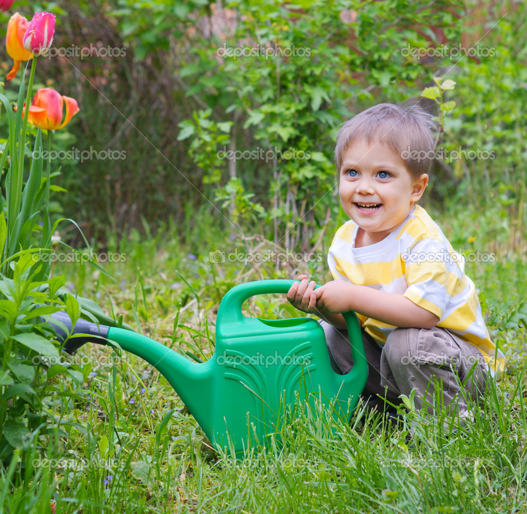 Cute little boy watering the flowers in the garden  Stock Photo #5642050
