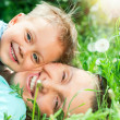 Cute boy with mother lying in the grass — Stock fotografie