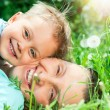Cute boy with mother lying in the grass — 图库照片