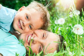 Cute boy with mother lying in the grass — Stock Photo