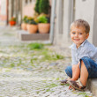 Little boy sits on the doorstep on a city street — Stock Photo