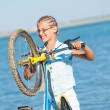 Beautiful young girl standing with her bicycle — Stock Photo