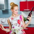 Blonde girl with glass and bottle of wine in interior of red kitchen — Stock Photo #5848129