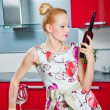 Blonde girl with glass and bottle of wine in interior of red kitchen — Stock Photo