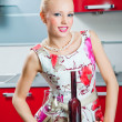 Blonde girl with glass and bottle of wine in interior of red kitchen - Stockfoto