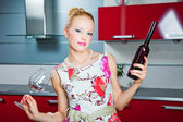 Blonde girl with glass and bottle with wine in interior of red kitchen — Stock Photo
