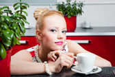 Girl with cup of coffee in interior of kitchen — Stockfoto