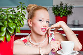 Sexy girl with cup of coffee in interior of kitchen — Stock Photo