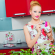 Blond girl in interior of red modern kitchen — Stock Photo