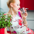 Blond girl drinking in interior of red modern kitchen — Stock Photo