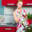 Blond girl with cup of coffee in interior of kitchen — Stock Photo #5895146