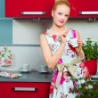 Blond girl with cup of coffee in interior of kitchen — Stock Photo