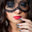Attractive brunette girl with lacy mask on her eyes — Stock Photo