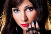 Beautiful brunette girl with fine art lacy manicure on black — Stock Photo