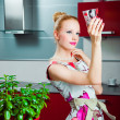 Housewife with clean glass in interior of kitchen — Stock Photo