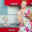 Stock Photo: Blond woman with cup of coffee in interior of kitchen