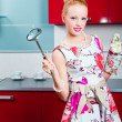 Blond girl ready for cooking in interior of red modern kitchen — Stock Photo