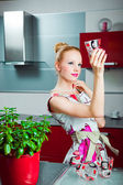 Ama de casa con vaso limpio en el interior de la cocina — Foto de Stock