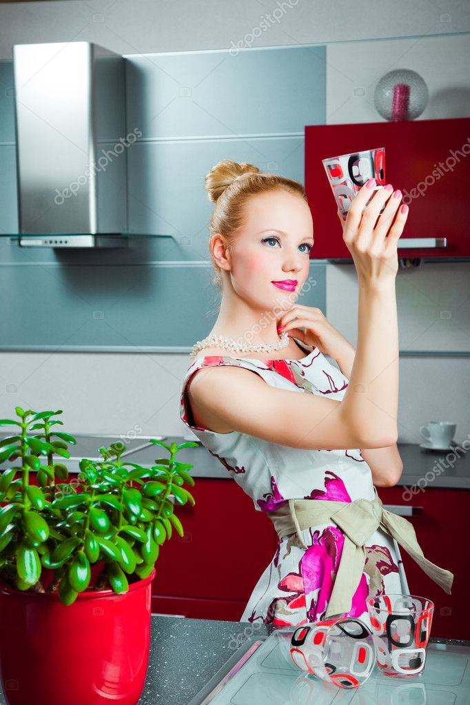 Young beautiful blond housewife wearing white and pink dress with clean glass in interior of red modern kitchen  Stock Photo #5975672