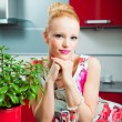 Blond girl with glass in interior of kitchen — Stock Photo