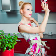 Housewife with clean glass in interior of kitchen - Foto de Stock