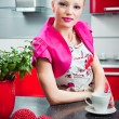 Blond girl in interior of red modern kitchen - Foto de Stock