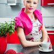 Blond girl in interior of red modern kitchen - Stockfoto