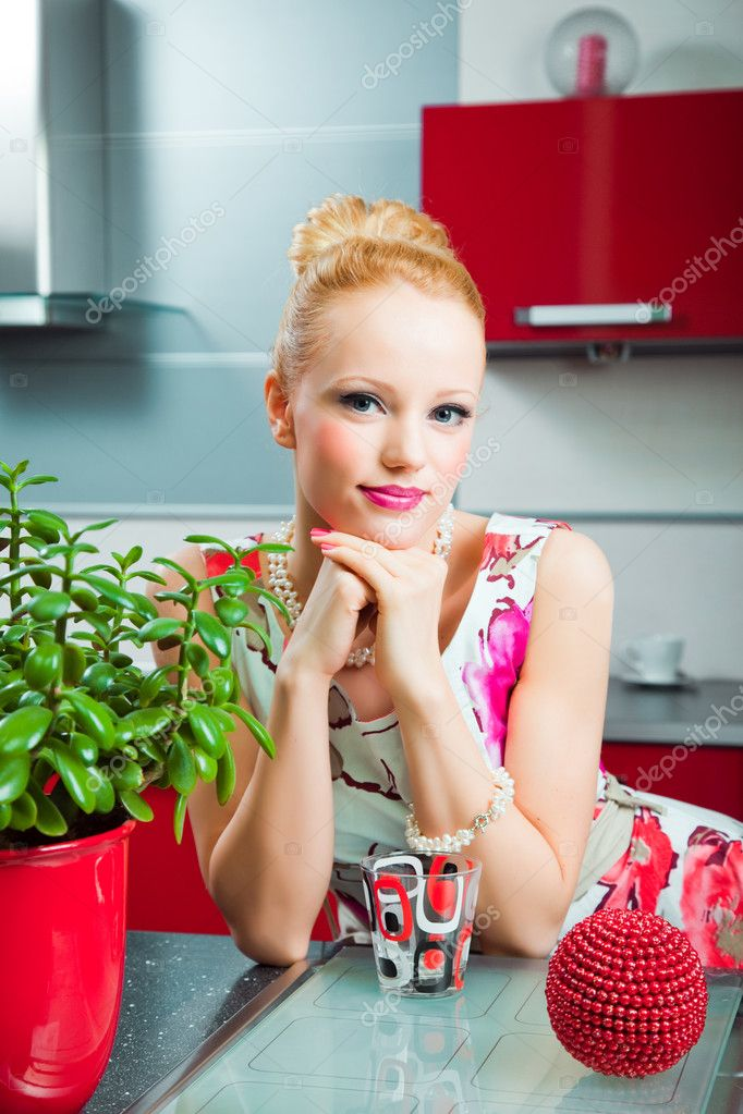 Young beautiful blond girl wearing white and pink dress with glass in interior of red modern kitchen — Stock Photo #6091303