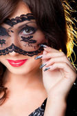 Attractive brunette with lacy mask on eyes — Stock Photo