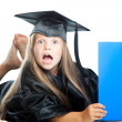 Cute little girl in graduation dress with blue book on isolated white — Stock Photo