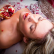 Lying woman with pomegranate — Stock Photo