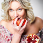 Blonde woman biting pomegranate on gray — Stock Photo